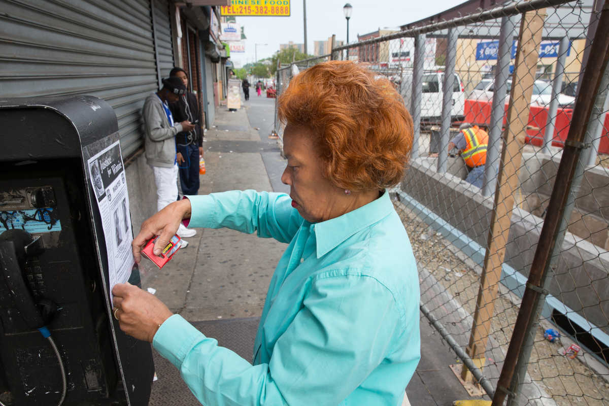 """Saundra Fulwood, friend of murder victim Winnie Harris, puts up """"Justice for Winnie"""" fliers at 40th and Market Streets on Tuesday, May 23, 2017."""