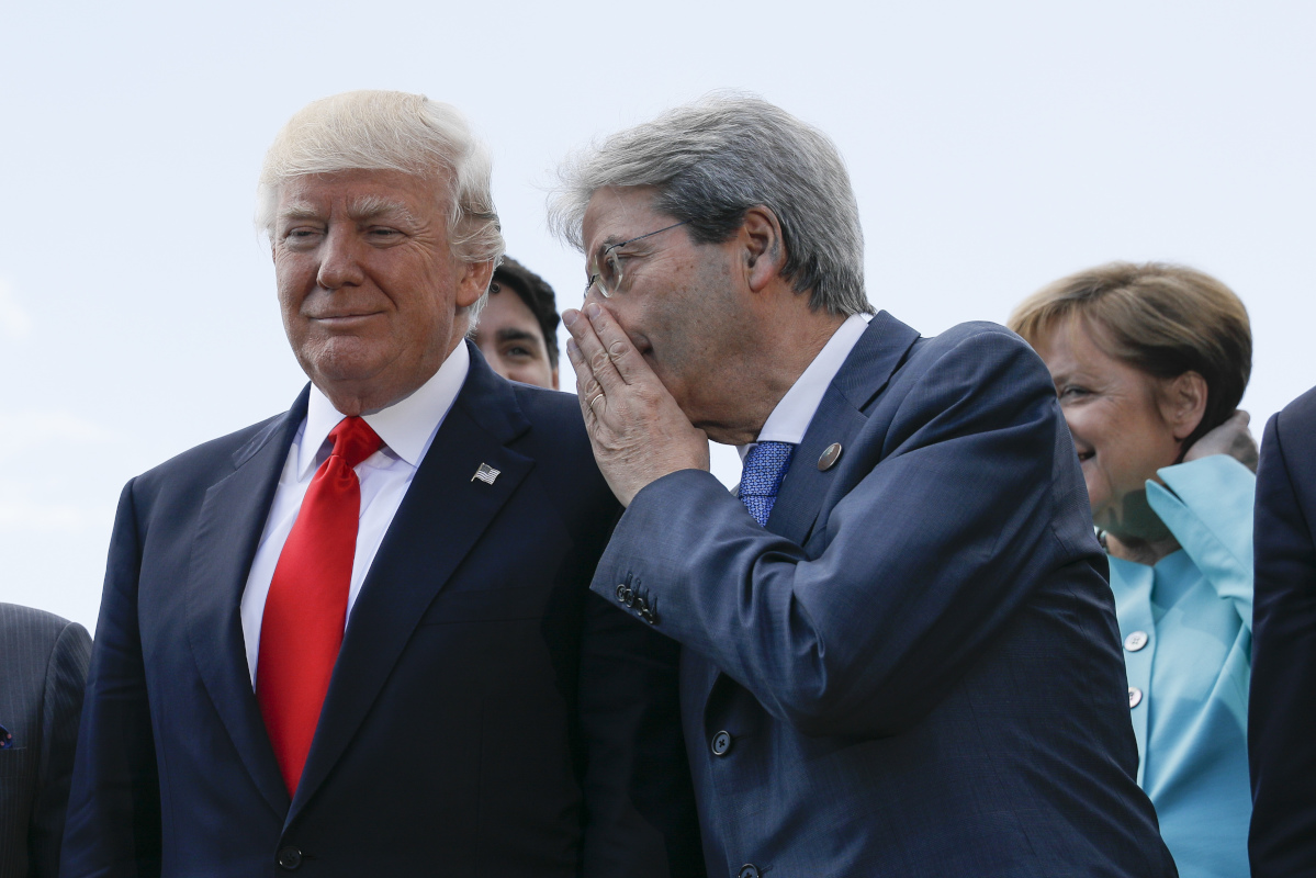 Italian Premier Paolo Gentiloni talks to U.S. President Donald Trump as the pose for a family photo with other G7 leaders and Outreach partners during a G7 summit in Taormina, Italy, Saturday, May 27, 2017.