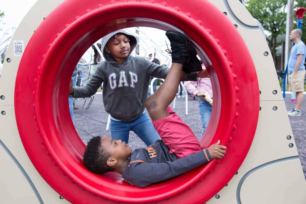 Seven-year-old Monet Parker, top center, and six-year-old Kasir Harris, bottom center, play on new playground equipment at the re-opening of Harold R. Brown Memorial Park, named for the first African-American soldier from Atlantic City to die in World War II, which officially opens today, Monday, May 29, 2017, after a $1.5 million renovation.