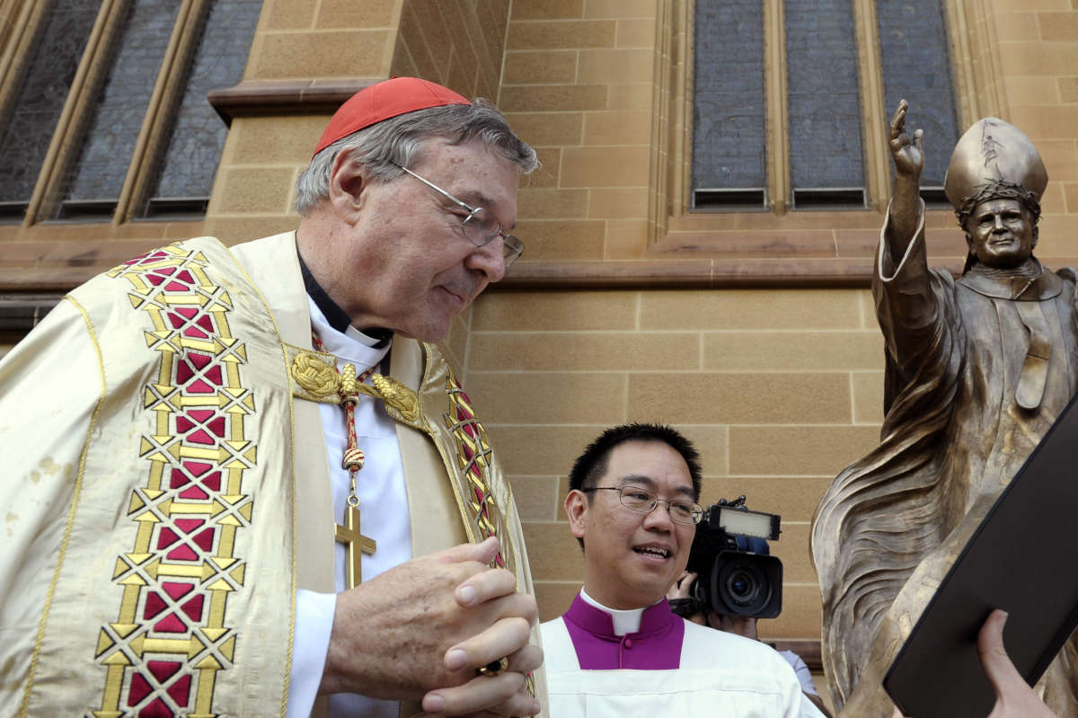 Cardinal George Pell (left) reads from the bible during the blessing of a statue of John Paul ll at St. Mary's Cathedral in Sydney, Australia. Australian police say they are charging Pell with sexual assault offenses.