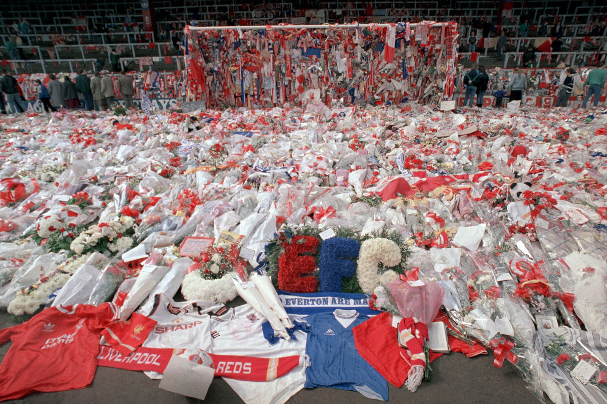 In this April 17, 1989 file photo, floral tributes are placed by soccer fans at the 'Kop' end of Anfield Stadium in Liverpool, England, two days after fans at Hillsborough Stadium surged forward during the FA cup semifinal between Liverpool and Nottingham Forest, killing 96 people.
