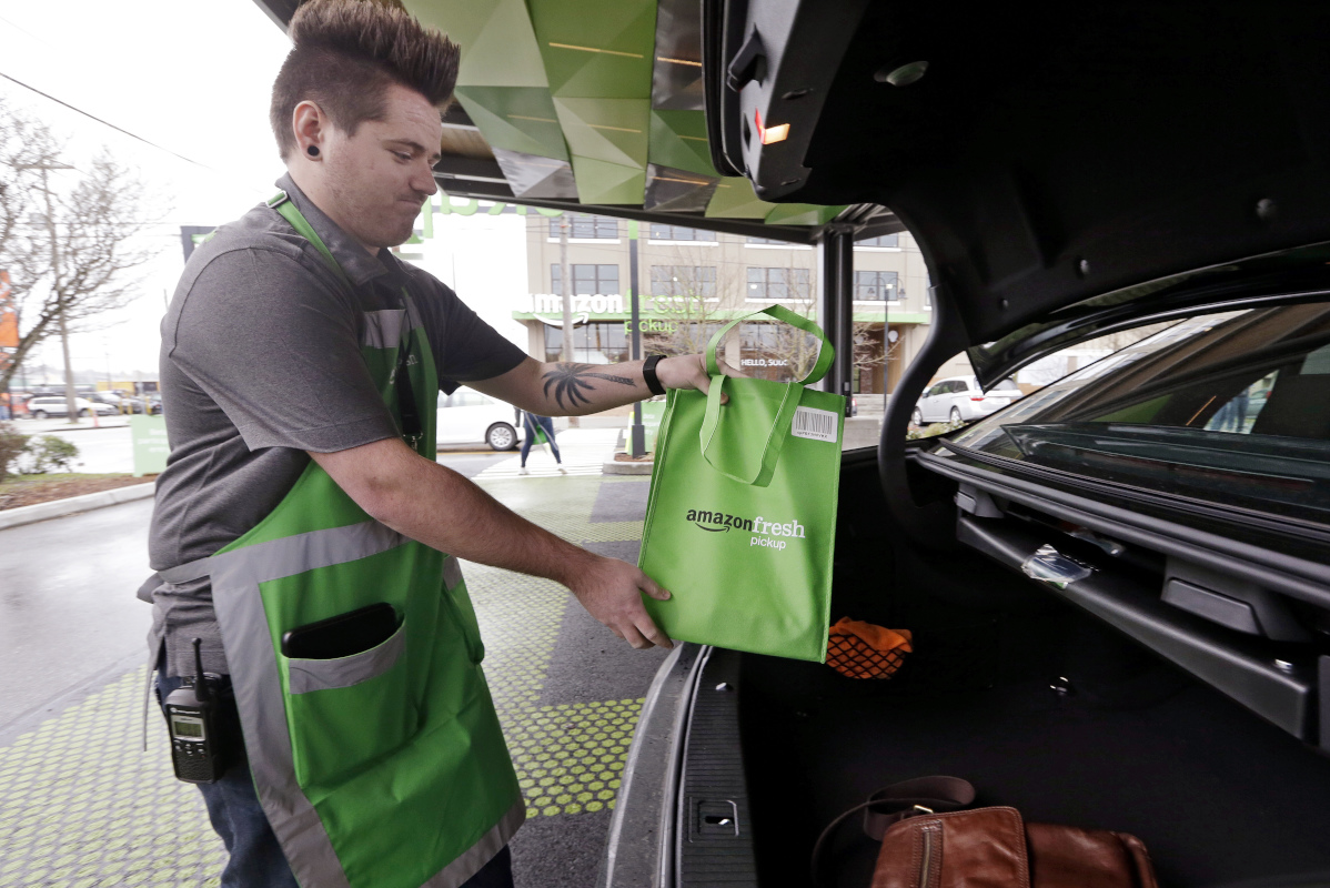 An Amazon worker, who declined to be identified, loads a bag of groceries into a customer's car trunk at an AmazonFresh Pickup location, Tuesday, March 28, 2017, in Seattle.