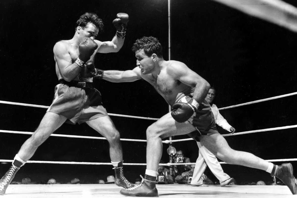 "Jake LaMotta (right) fights Marcel Cerdan in Briggs Stadium in Detroit in 1949.  LaMotta knocked out Cerdan in the 10th round to become the  world middleweight champion. LaMotta, whose life was depicted in the film ""Raging Bull,"" died Tuesday."