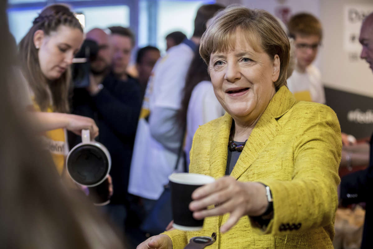 German chancellor Angela Merkel drinks a cup of coffee with election campaign workers in Berlin, Saturday, Sept. 23, 2017 ahead of Germany's election on Sunday.
