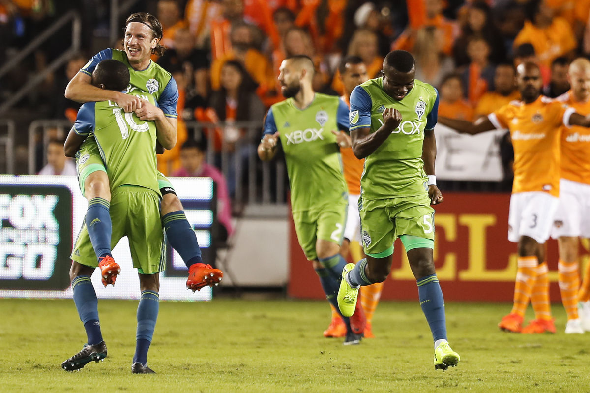 Seattle Sounders defender Gustav Svensson (4) and defender Kelvin Leerdam (18) celebrate Svensson's goal against the Houston Dynamo during the first half.