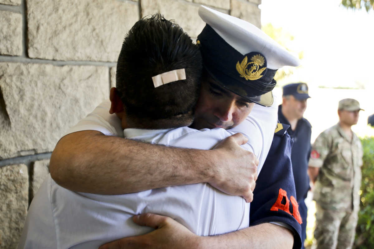 Argentine navy officials embrace inside the Mar de Plata Naval Base after hearing that a sound detected during the search for the missing ARA San Juan submarine is consistent with that of an explosion.