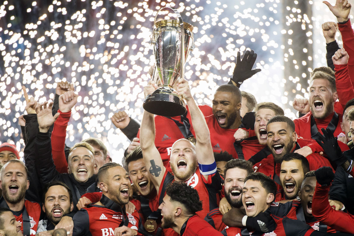 Toronto FC captain Michael Bradley hoists the trophy as the team celebrates its win over the Seattle Sounders in the MLS Cup final.
