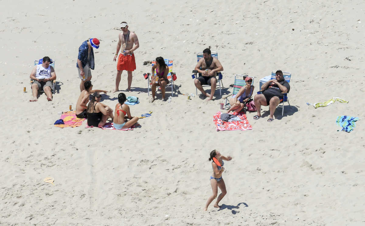 FiLE - In this Sunday, July 2, 2017 file photo, New Jersey Gov. Chris Christie, right, uses the beach with his family and friends at the governor´s summer house at Island Beach State Park in New Jersey. New Jersey Gov.-elect Phil Murphy is getting some pushback for posing for photos on Thursday, Dec. 14, 2017, next to a cardboard cutout of Christie lounging on a beach last summer. Christie came under intense criticism for using the beach closed to the public over the Fourth of July weekend due to a government shutdown.