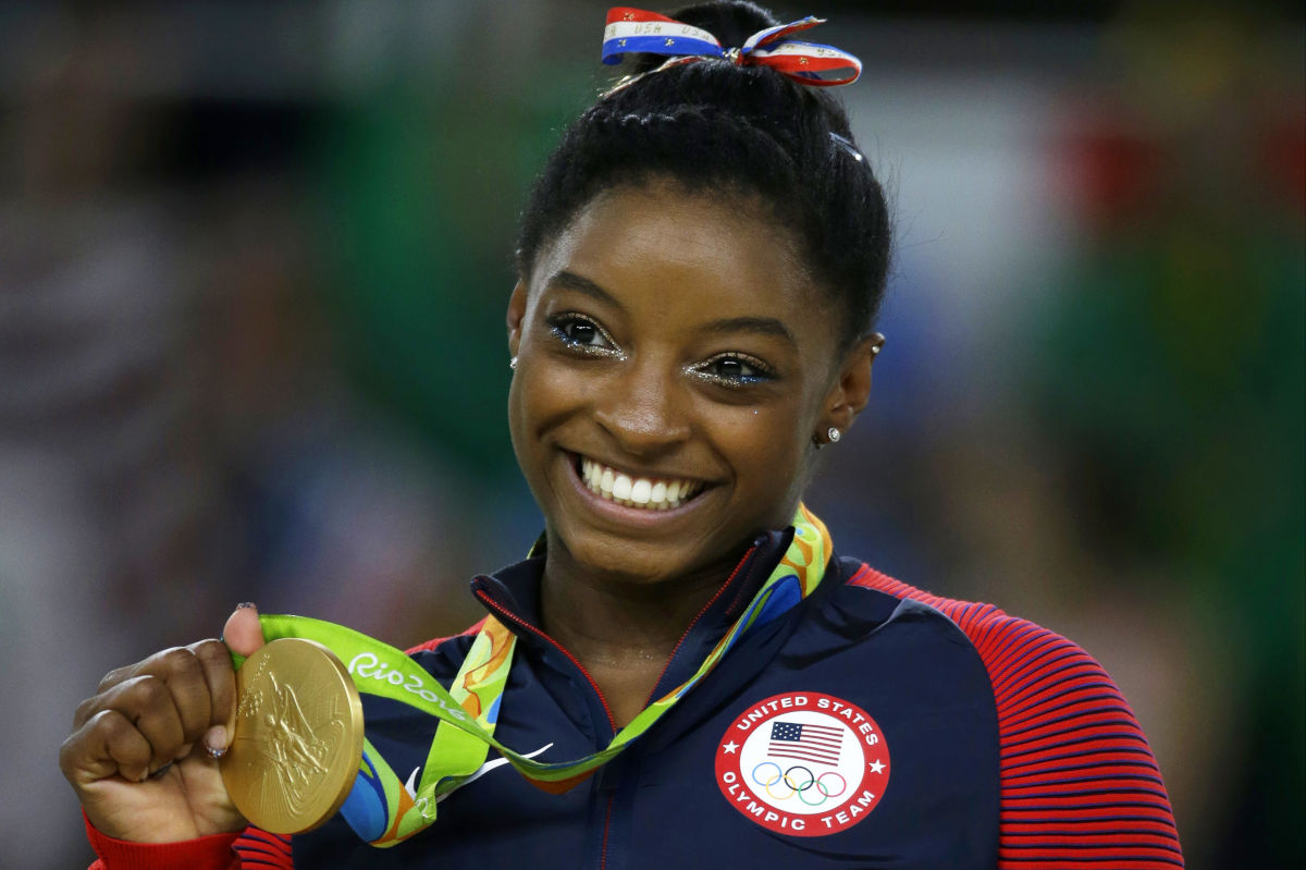 FILE - In this Aug. 16, 2016 file photo, United States gymnast Simone Biles displays her gold medal for floor during the artistic gymnastics women&acute;s apparatus final at the 2016 Summer Olympics in Rio de Janeiro, Brazil. In a statement via Twitter on Monday, Jan. 15, 2017, Biles says she is among the athletes sexually abused by a now-imprisoned former USA Gymnastics team doctor.<br />