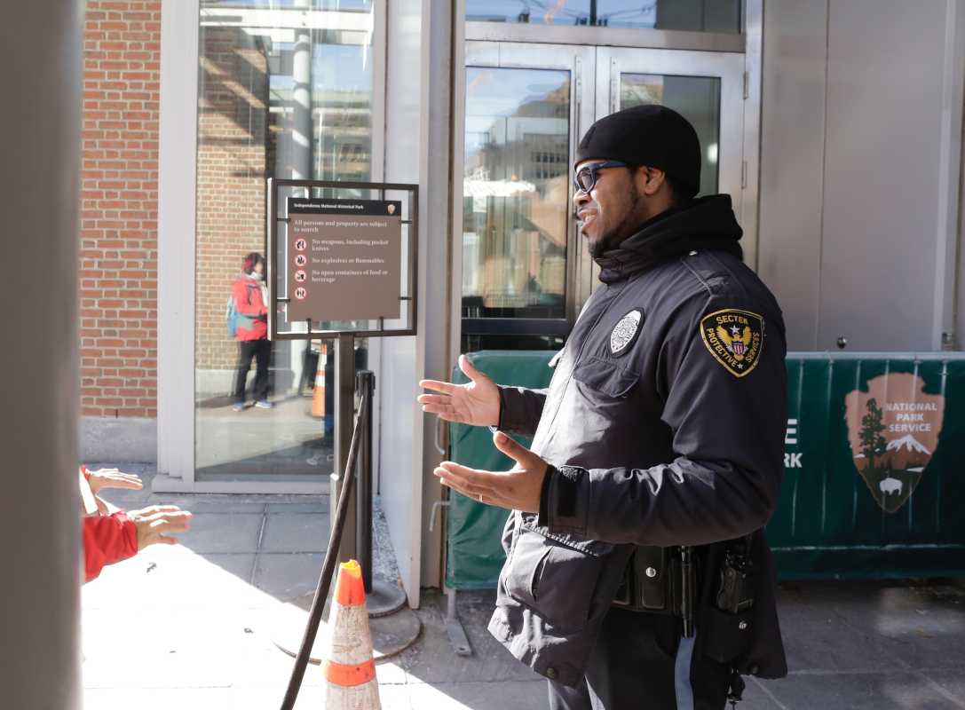 A Sector Protective Services security guard at the  Liberty Bell Center in Independence National Historical Park in Phila., Pa. informs visitors that the building is closed because of the US government shutdown on Jan. 20, 2017.