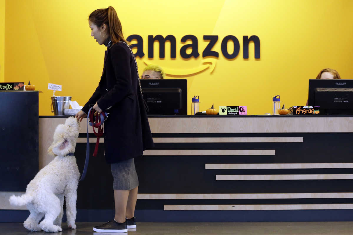 In this Wednesday, Oct. 11, 2017, file photo, an Amazon employee gives her dog a biscuit as the pair head into a company building, where dogs are welcome, in Seattle. Amazon announced Thursday, Jan. 18, 2018, that it has narrowed its hunt for a second headquarters to 20 locations, concentrated among cities in the U.S. East and Midwest. Toronto made the list as well, keeping the company's international options open.
