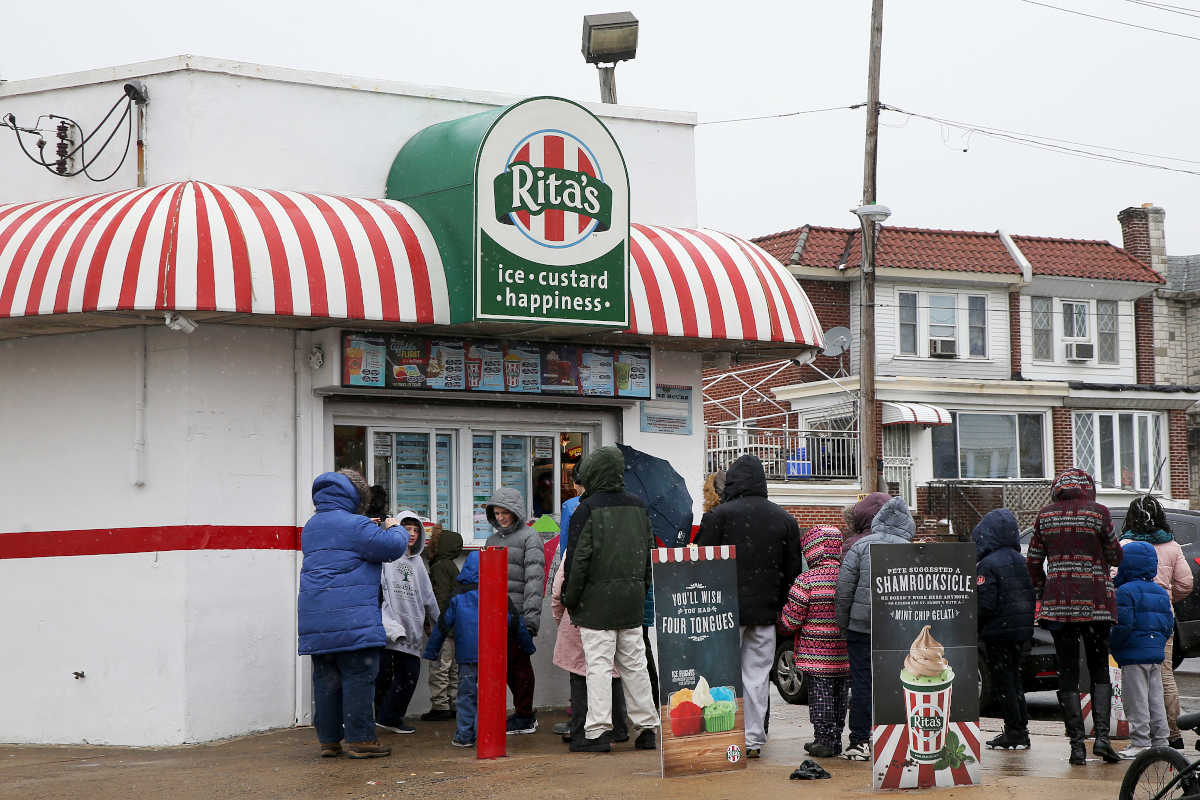 Customers wait in line amid snow and freezing rain for free ice to celebrate the first day of spring at Rita's Water Ice in Olney on Tuesday, March 20, 2018.