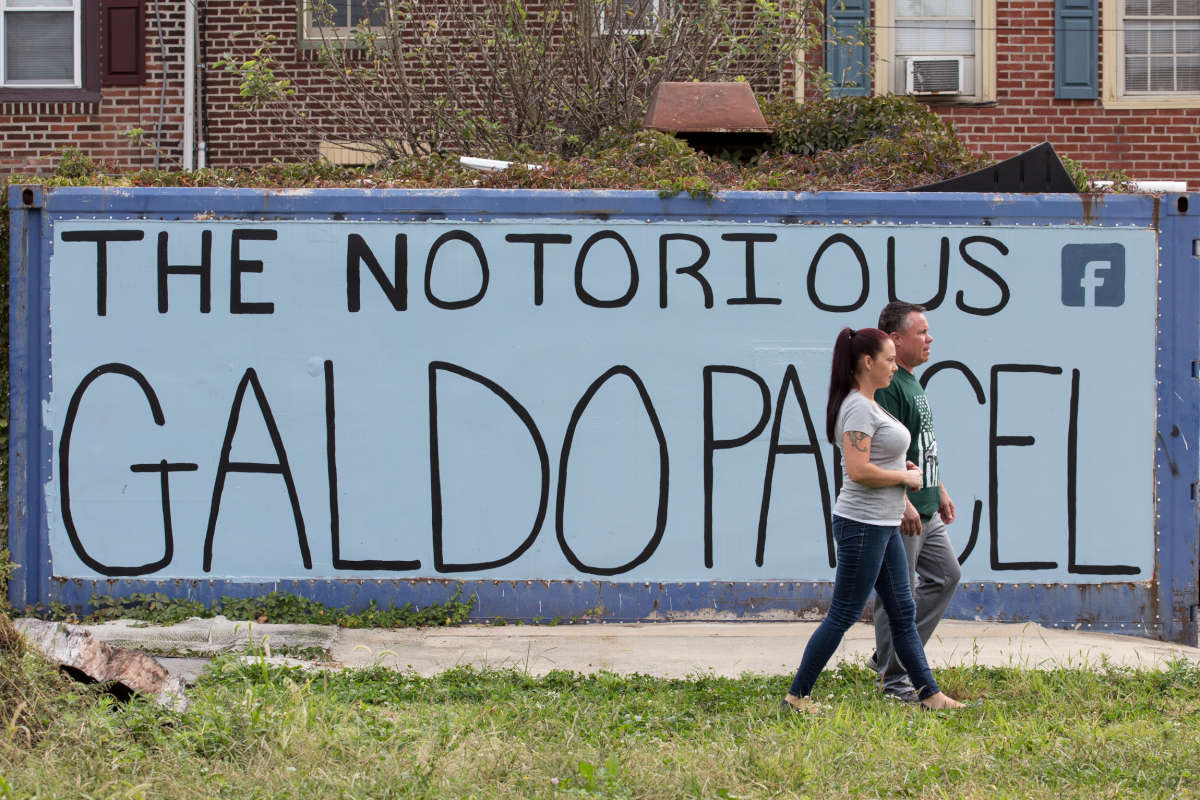 """Frank Galdo, back, and his wife Nicole Galdo, front, shown here on the vacant lot across the street from their house, Frank has been maintaining and improving the lot for over twenty years, in Fishtown, Wednesday, Oct. 11, 2017. The couple are walking in front of a large sign publicizing their plight. Galdo paved a driveway, built a fire pit and a treehouse, but the city wants the land back. Galdo lost the first round in court, and is pursuing an appeal using an """"adverse possession"""" legal argument. JESSICA GRIFFIN / Staff Photographer"""