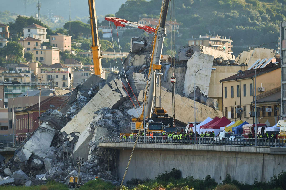 Rescuers search the crumbled hulk of the collapsed Morandi highway bridge in Genoa, northern Italy, on Wednesday.