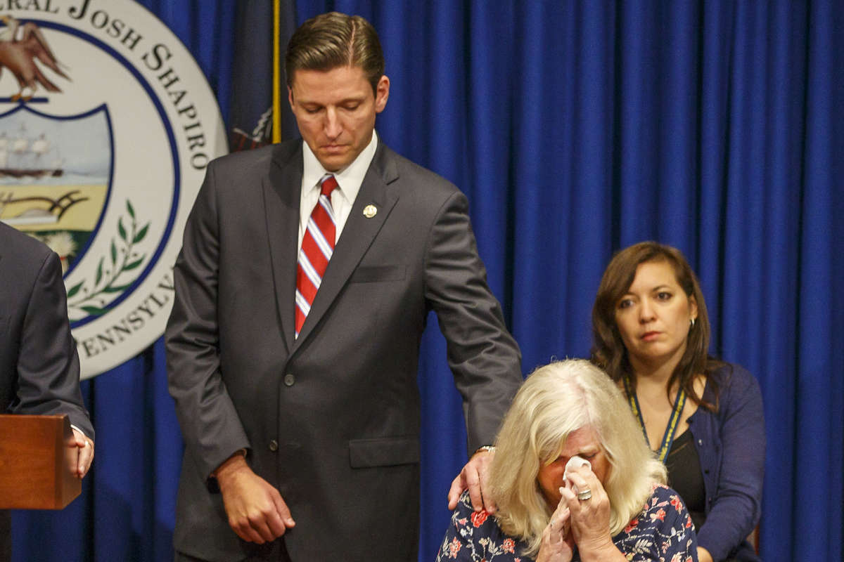 Daniel J. Dye (center), senior deputy attorney general, reaches over and comforts Judy Deavena (right), mother of Joey Behe, a victim of sexual abuse from a Catholic priest.