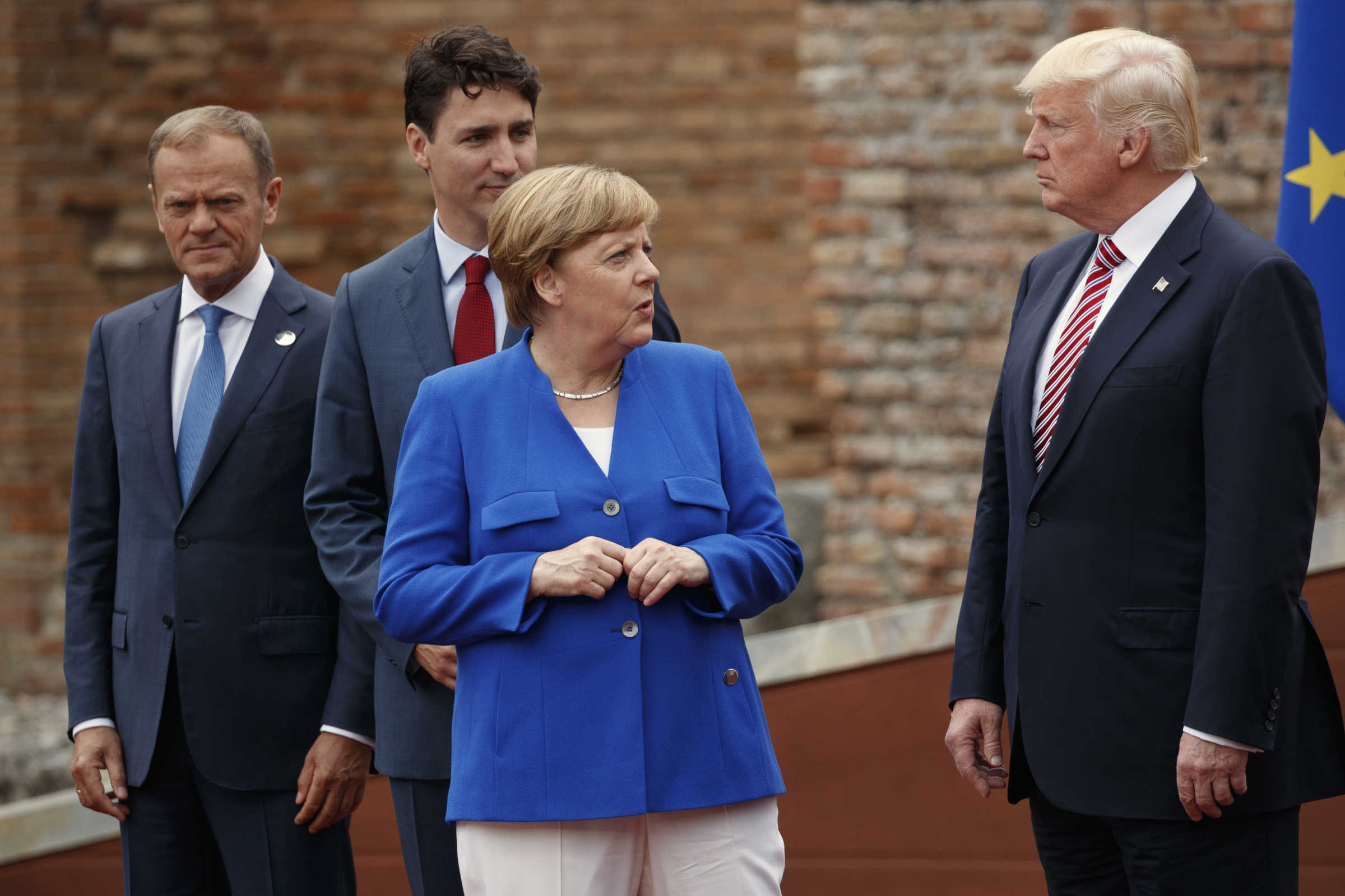 German Chancellor Angela Merkel talks with President Donald Trump during a family photo with G7 leaders at the Ancient Greek Theater of Taormina, Italy.