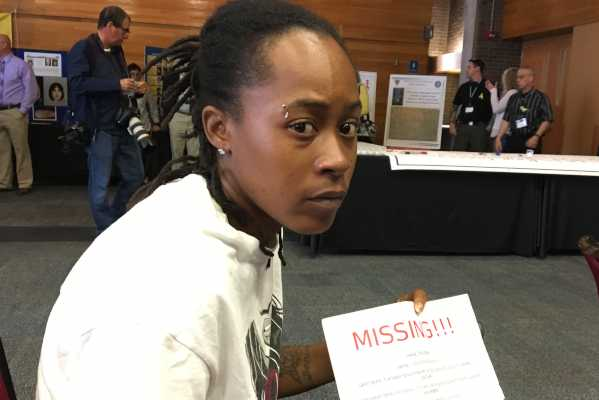 Denisha Molley holds up a poster seeking information on her missing brother, Dashand Stokelin, of Atlantic City, who went missing Nov. 22, 2016.