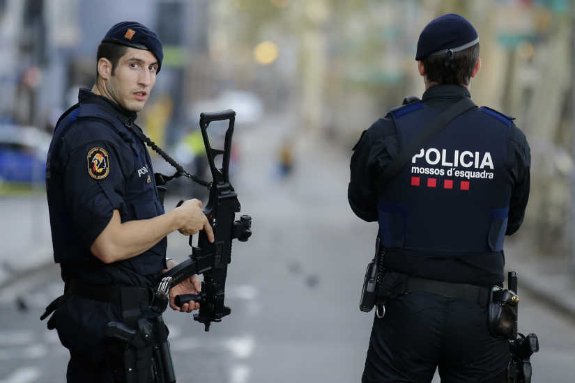 Armed police officer stand in Las Ramblas, Barcelona, Spain, Friday, Aug. 18, 2017. Spanish police on Friday shot and killed five people carrying bomb belts who were connected to the Barcelona van attack that killed at least 13, as the manhunt intensified for the perpetrators of Europe's latest rampage claimed by the Islamic State group.