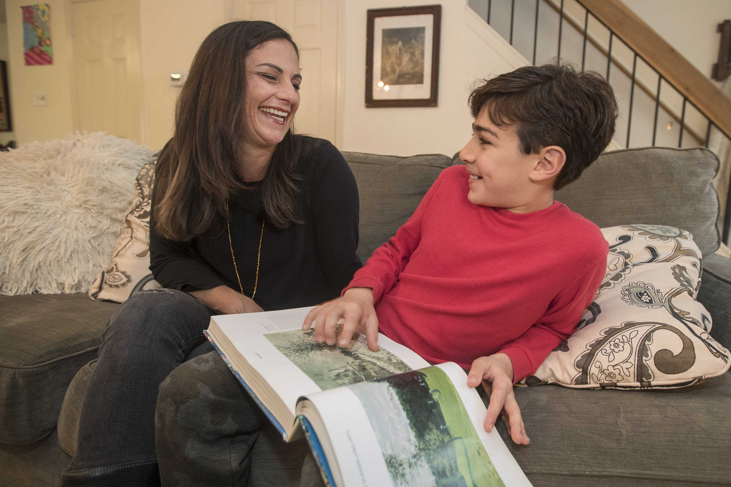 Erica Daniels shares a funny moment with her 12-year-old son, Leo, as they look through a book about Monet, Leo's favorite artist.