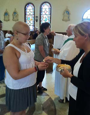 Rachel takes Communion at Mass – without crutches. (Photo: Kurt Kovach)