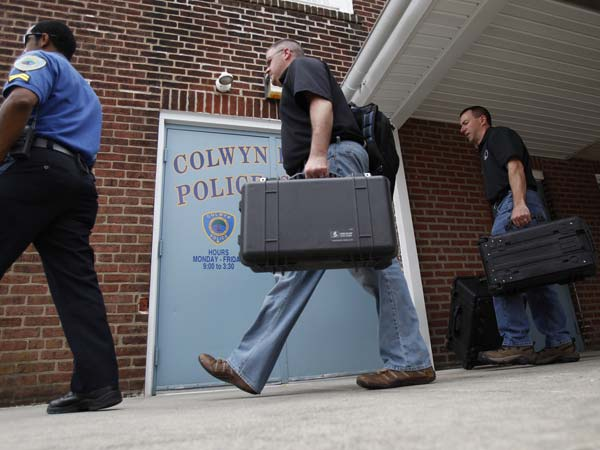 FBI agents leave the Colwyn Borough Police Station on May 9, 2013. They also visited the borough hall building. ( DAVID MAIALETTI / Staff Photographer )<br />