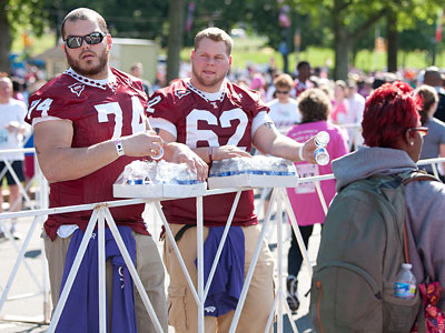 Temple offensive linemen Evan Regas (74) and Scott Roorda (62) gave out water bottles during last year's Susan G. Koman Philadelphia Race for the Cure. Regas' mother, Susan Untoria, learned last week that her breast cancer is in remission. (Mitch Leff/Temple University)