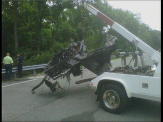 "A tow truck hauls away the wreckage from the car crash that left ""Jackass"" star Ryan Dunn and a passenger dead."