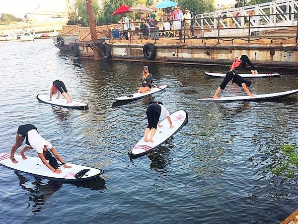 A standup paddleboard yoga class by Aqua Vida at Spruce Street Harbor Park.