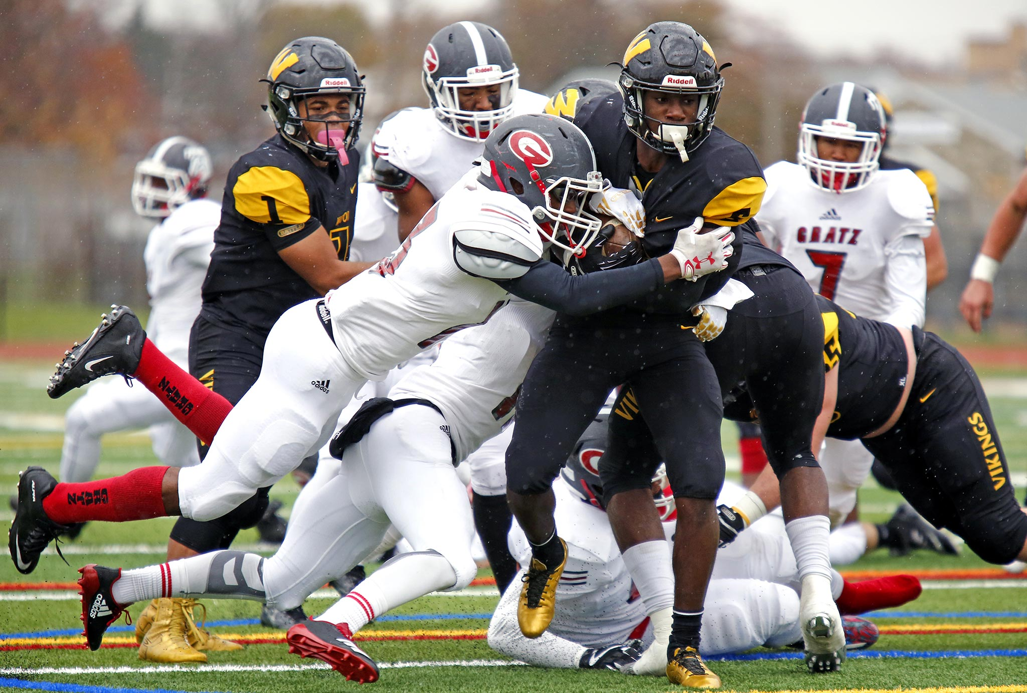 Archbishop Wood running back Nasir Peoples carries Simon Gratz defender Jawon Harrison (middle, airborne) and Terrell Stewart (hidden) for yardage during the second quarter of the District 12 Class 5A football final Saturday, Nov. 18, 2017, at Northeast High. Wood went on to win, 36-6.