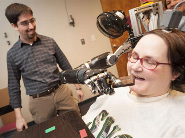 Jan Scheuermann, who has quadriplegia, takes a bite out of a chocolate bar she has guided into her mouth with a thought-controlled robot arm. (Credit UPMC)