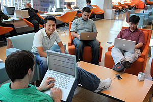 Sean Brown (facing camera), a director of engineering for Fancast.com, sits with some team members in the company's 15th-floor CIM City lounge, the focal point for Comcast Interactive Media. The space offers abundant comfortable seating for getting work done, and plenty of diversions for clearing the mind or keeping the creative juices flowing.<br />