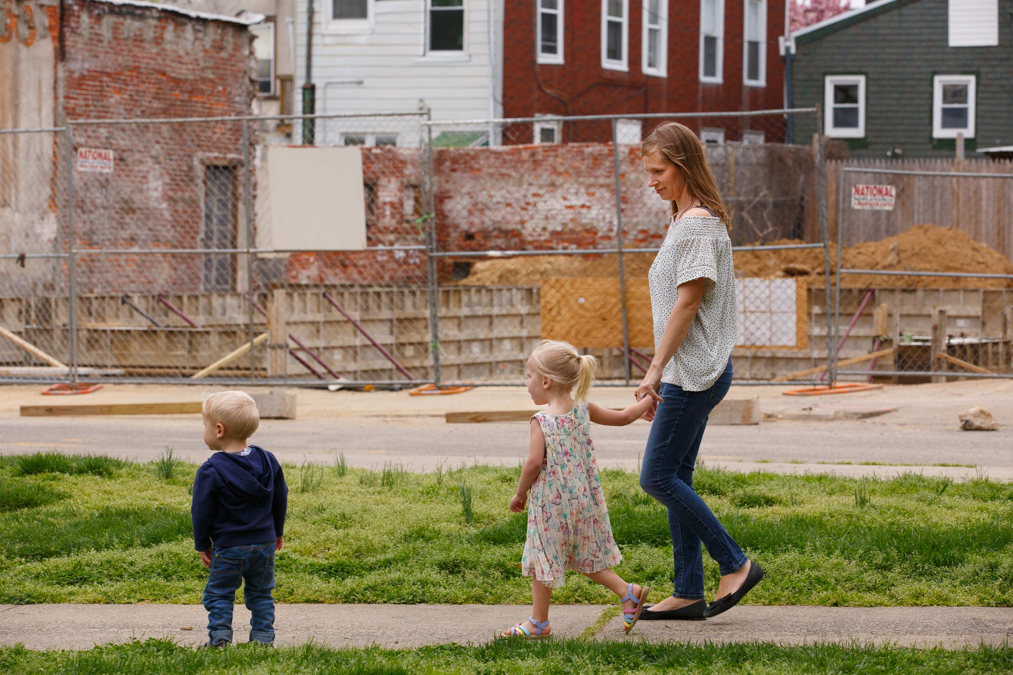 Jana Curtis walks with her children past a construction site near their neighborhood park in Kensington. After her yard´s soil tested high for lead, Curtis learned that her daughter, Nolyn, had lead poisoning. Nolyn struggles with her speech and temper.