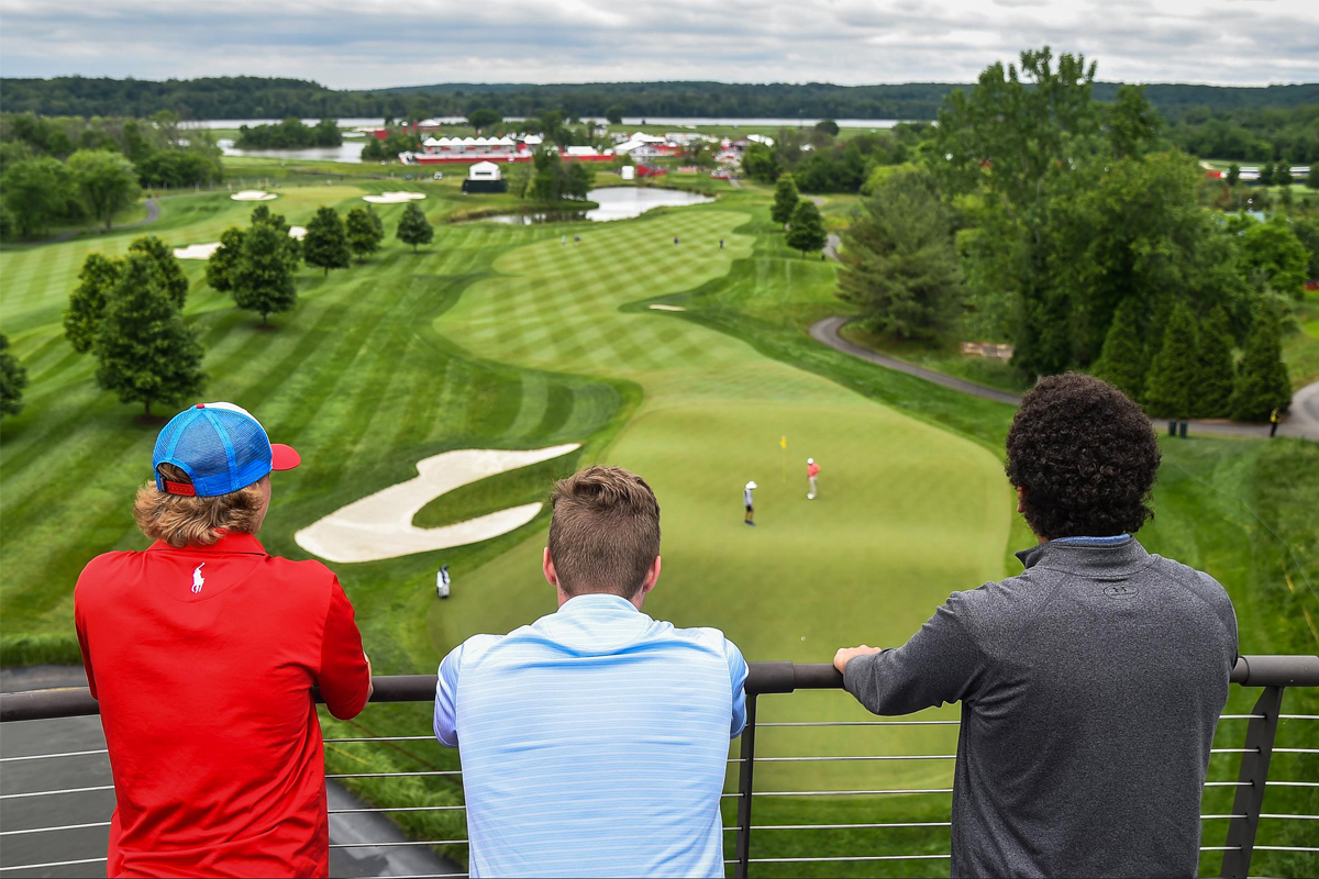 Spectators watch golfers practicing at the Trump National Golf Club.<br />