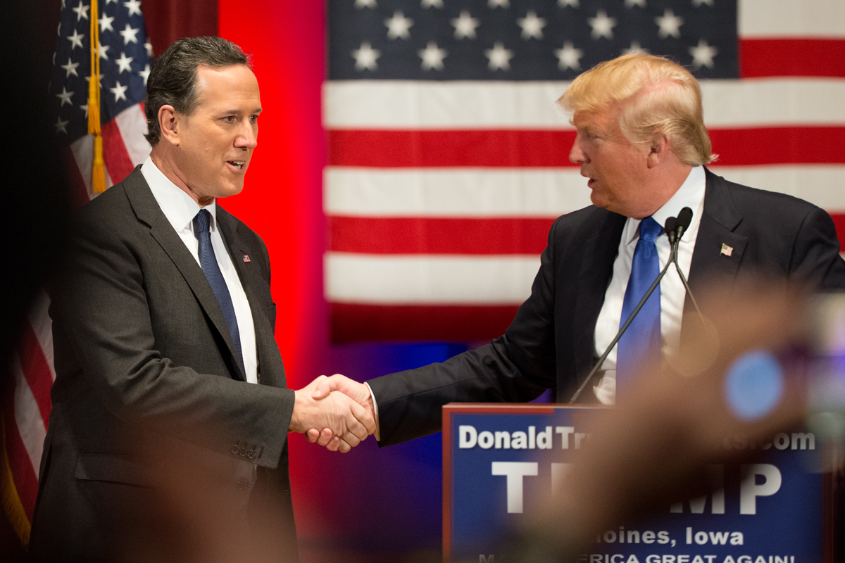 Former Pa. senator Rick Santorum (left) stands beside then-presidential candidate Donald Trump in Iowa in January 2016. These days, Santorum is one of a handful of analysts paid by CNN to defend Trump´s administration.