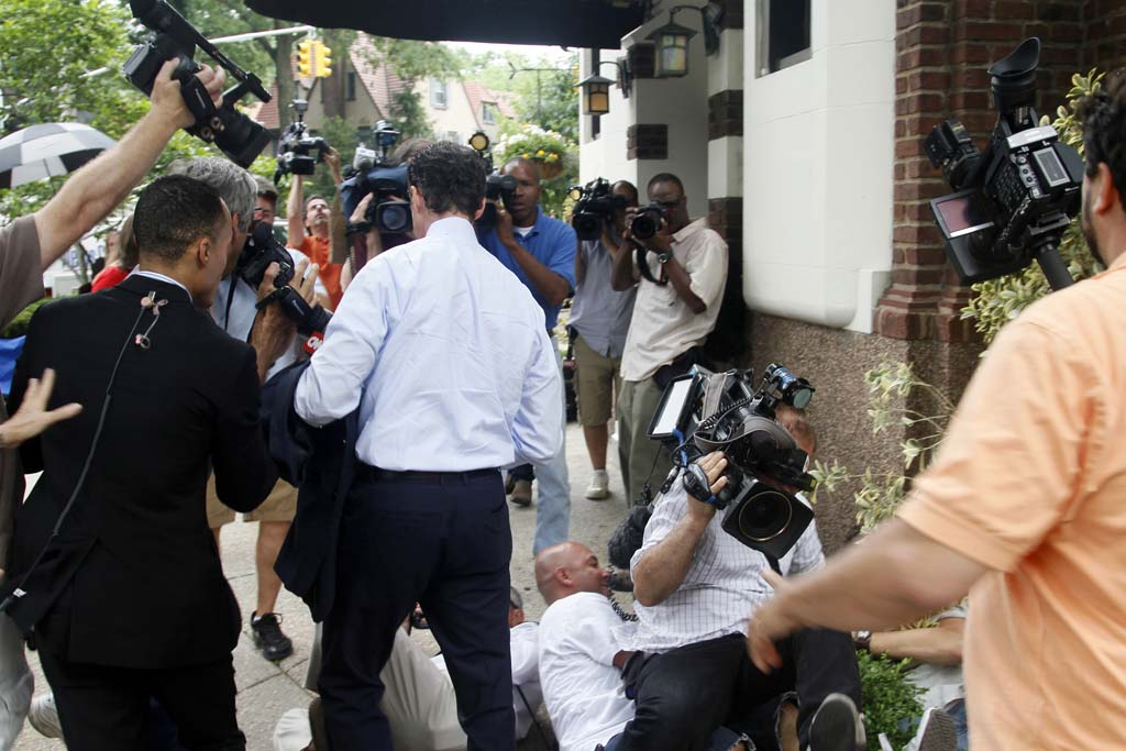 News photographers fall while scrambling to cover Anthony Weiner,  as he return home from a news conference, Thursday, June 16, 2011, in the Queens borough of New York.  Weiner resigned from Congress, saying he cannot continue in office amid the intense controversy surrounding sexually explicit messages he sent online to several women. (AP Photo/Bebeto Matthews)