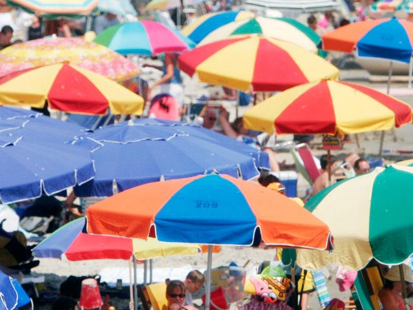 Colorful umbrellas shield beach goers from the intense sun in Ocean City, NJ. (Eric Mencher/Staff)