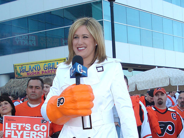 "In this 2008 photo, Jamie Apody of 6ABC does her sports report with a Flyers ""drinking glove.""( FILE PHOTO - ERIC MENCHER / Inquirer Staff Photographer )"