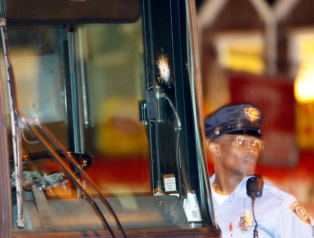An officer examines a bullet hole on a SEPTA bus that was involved in a shooting near Cheltenham and Ogontz avenues, on Tuesday, September 13, 2011.  (Yong Kim / Staff Photographer)