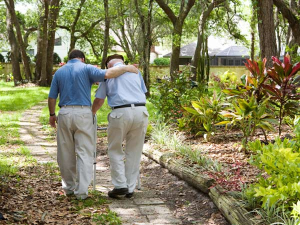 Man walking with father in park.