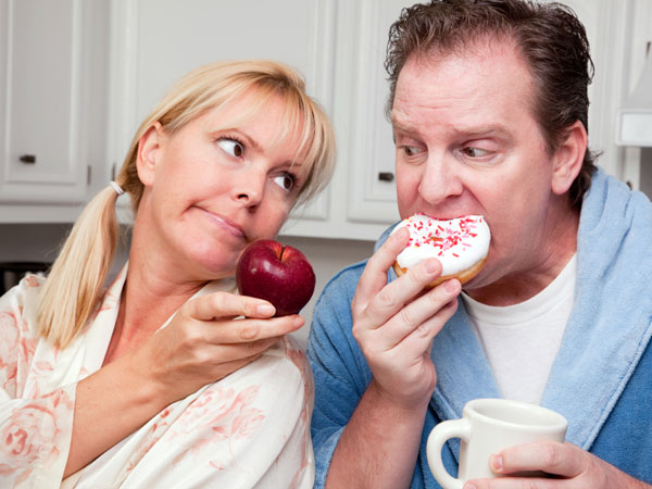 She´s trying to get her husband to trade the doughnuts for apples.