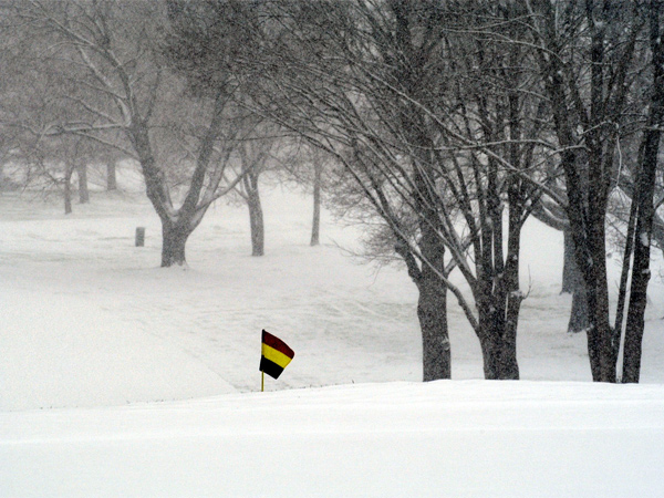 On April 7, 2003, a flag sticks through the snow that fall at Philadelphia Cricket Club golf course on Valley Green Road in Whitemarsh. (Photo by Hinda Schuman / Staff Photographer)
