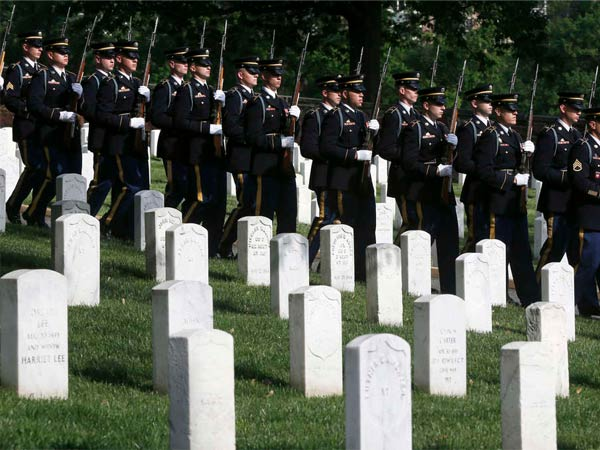 An Army honor guard stands at the grave site of Army Pvt. William Christman, the first military burial at the cemetery in 1864, marking the start of the 150th anniversary of Arlington National Cemetery.