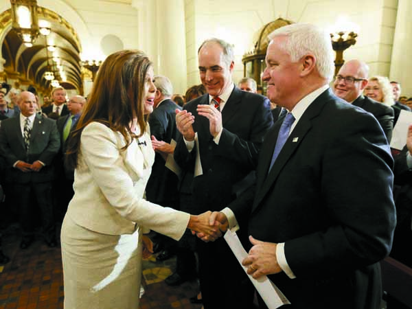 Gov. Tom Corbett, right, and Sen. Bob Casey, D-Pa., second left, greet, Kathleen Kane, center, before she took her oath of office for Pennsylvania Attorney General at the state Capitol in Tuesday, Jan. 15, 2013, in Harrisburg, Pa. Kane is first woman and first Democrat to be elected Pennsylvania attorney general. (AP Photo/Matt Rourke)