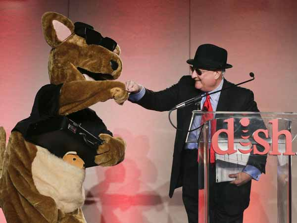 DISH Network president and CEO Joe Clayton greets the company mascot, Hopper, at the start of a news conference during press day at the Consumer Electronics Show, Monday, Jan. 7, 2013, in Las Vegas. (AP Photo/Julie Jacobson)