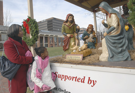 Joanne Jackson and daughter Aniesha, 7, of Philadelphia look<br />at the Nativity scene at Independence Mall that has a new Jesus. The original plastic baby and his cradle disappeared two weekends ago.