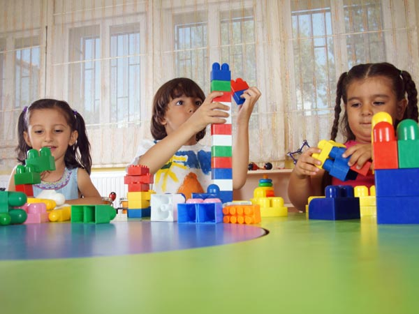 Preschool children playing with building blocks.