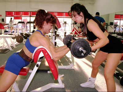 Dolores M. Gurule de Duran powers her way through a lift at a gym in Albuquerque, N.M., Thursday, April 10, 1997, while workout partner Kimberly Lucero spots. The 37-year-old police officer and bodybuilder was training for the 1997 World Police and Fire Games running through Friday in Alberta, Canada. (AP Photo/ Albuquerque Journal)