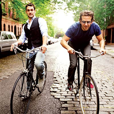 """Hangover"" stars Justin Bartha and Bradley Cooper ride bikes. Cooper is one of the 84th Academy Awards show´s presenters."