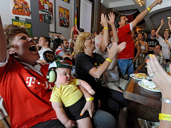 Eight-month-old Robert Hill, in headphones and a German beanie, naps through the U.S.-Germany World Cup game on grandmother Jo Loeffler's lap at Brauhaus Schmitz Thursday, June 26, 2014. His German grandfather, Mirko Loeffler (back left), roots for his home team. (CLEM MURRAY / Staff Photographer)