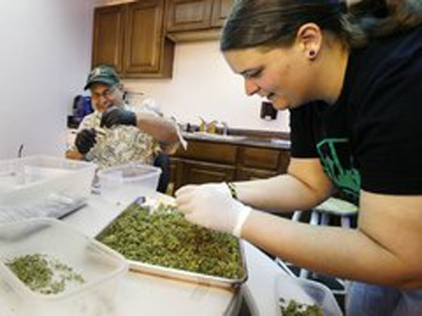 "In this photo taken July 1, 2014, workers Kristi Tobias, right, and Bruce Cumming prepare packets of a variety of recreational marijuana named ""Space Needle"" at Sea of Green Farms in Seattle. Workers at the grower, the first business licensed to grow recreational marijuana in Washington state, worked all weekend to have supplies ready for stores that were expected to be granted sale licenses on Monday, the day before the first day of legal recreational pot sales in Washington state. (AP Photo/Ted S. Warren)"